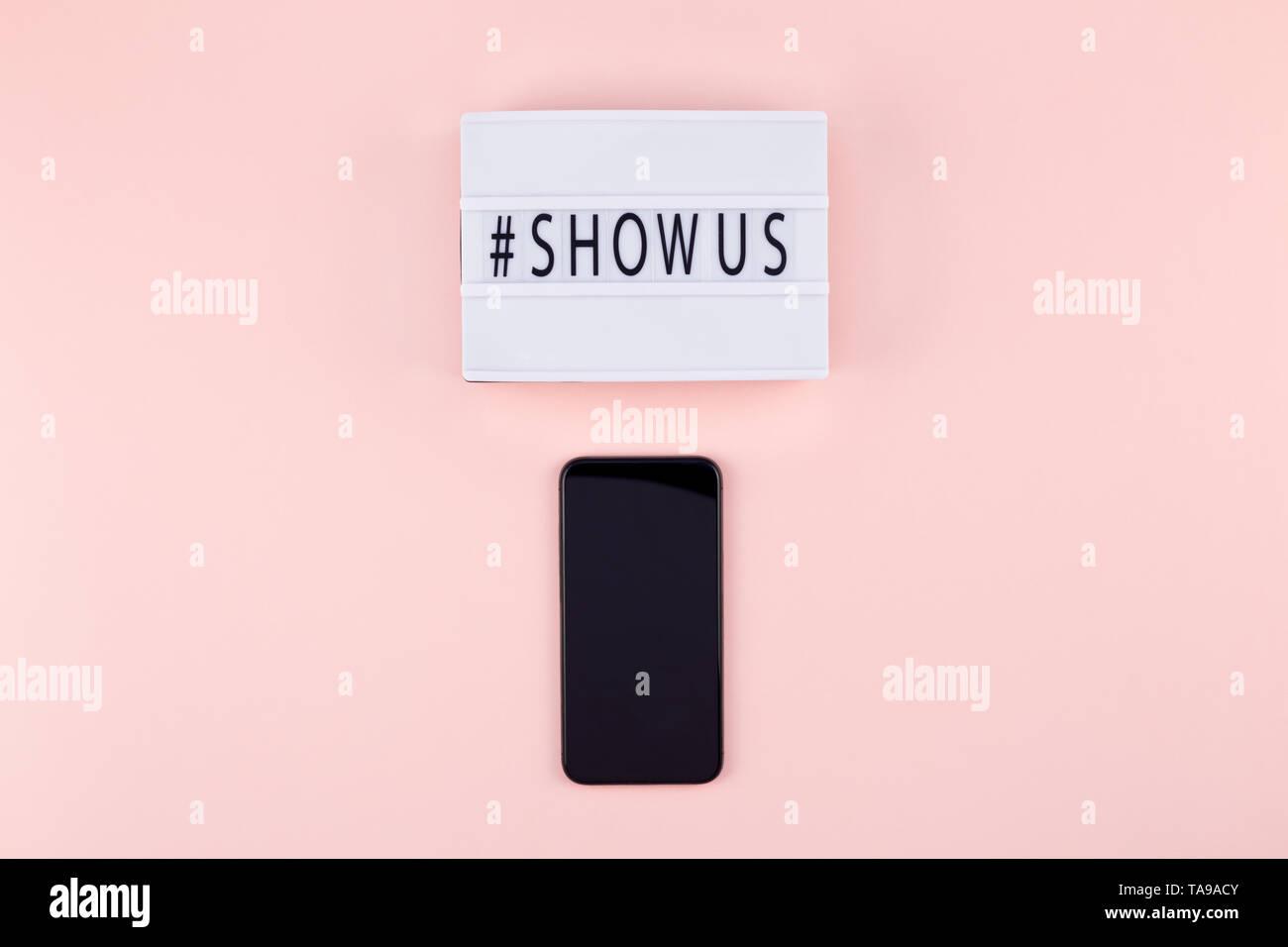 Kreative, oben flach der Lightbox mit hashtag zeigen uns Nachricht und Mobiltelefon mockup rosa Hintergrund minimal Style. Konzept des Projekts Welt la Stockbild