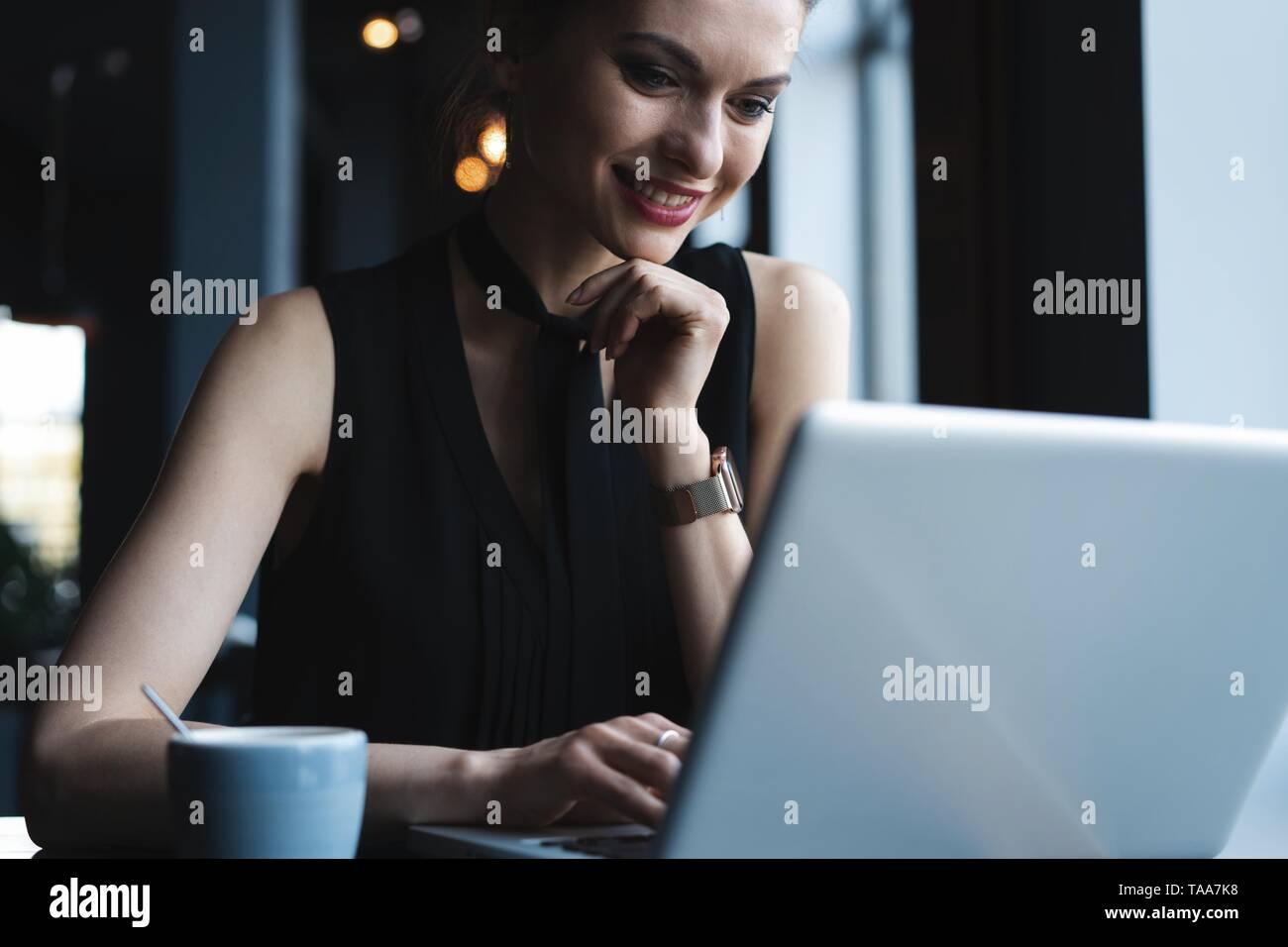 Bei der Arbeit konzentriert. Selbstbewussten jungen Frau in Smart Casual Wear Arbeiten am Laptop, während in der Nähe der Fenster in kreative Büro oder Cafe sitzen. Stockfoto