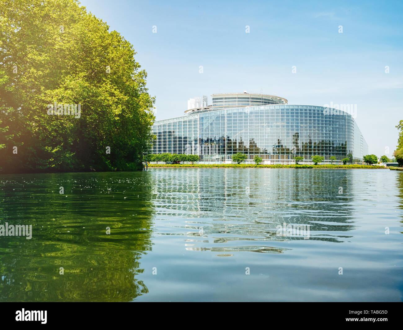 Low Angle View der breiten Fassade Hauptsitz des Europäischen Parlaments in Straßburg einen Tag vor 2019 zu den Wahlen zum Europäischen Parlament - klaren blauen Himmel und ruhige Ill Wasser Sonnenlicht Flare. Stockfoto