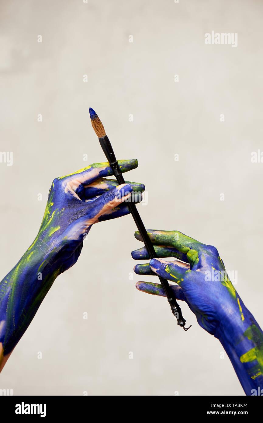 Anmutigen Händen der Künstler mit einer Bürste. Hände in blauer und gelber Farbe. Schöpfer, Kreativität. Stockbild