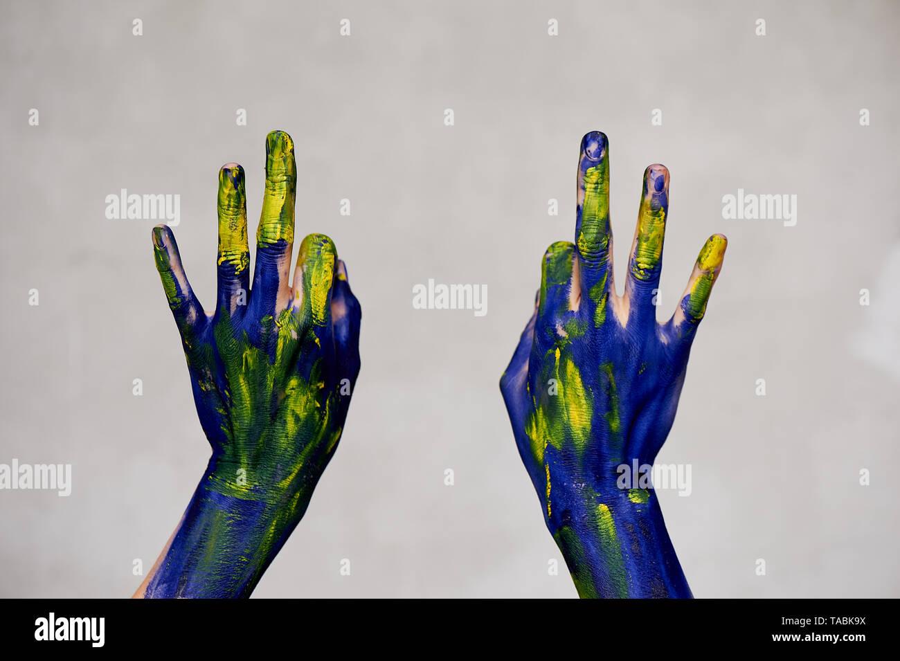 Anmutigen Händen des Künstlers. Hände in blauer und gelber Farbe. Schöpfer, Kreativität. Yoga für die Hände Stockbild