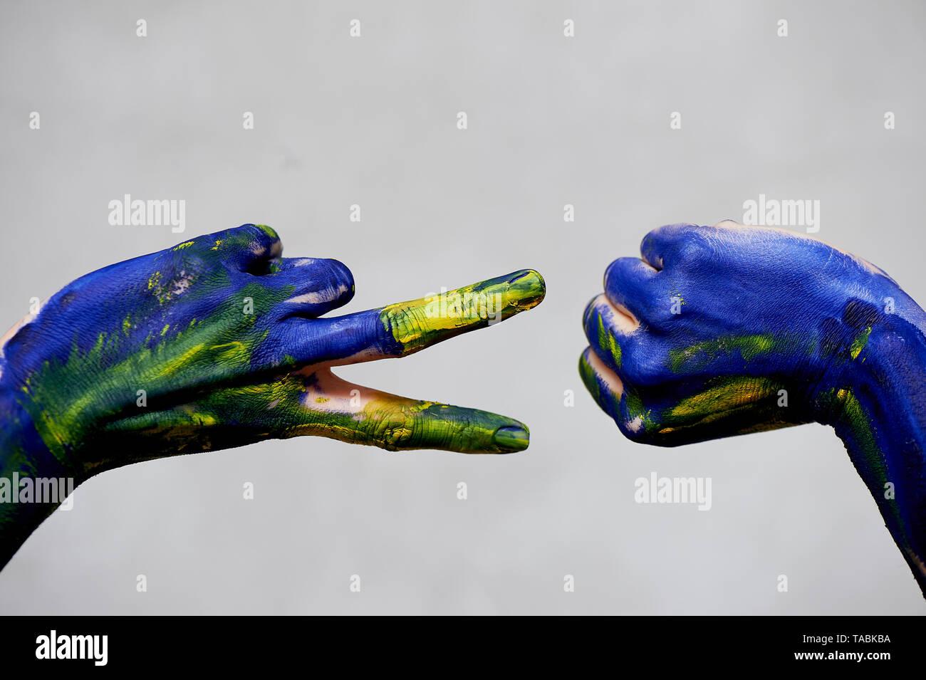 Anmutigen Händen des Künstlers. Hände in blauer und gelber Farbe. Schöpfer, Kreativität. Yoga für die Hände. ein Spiel von Rock Paper Scissors. Stein Schere, Hand i Stockbild