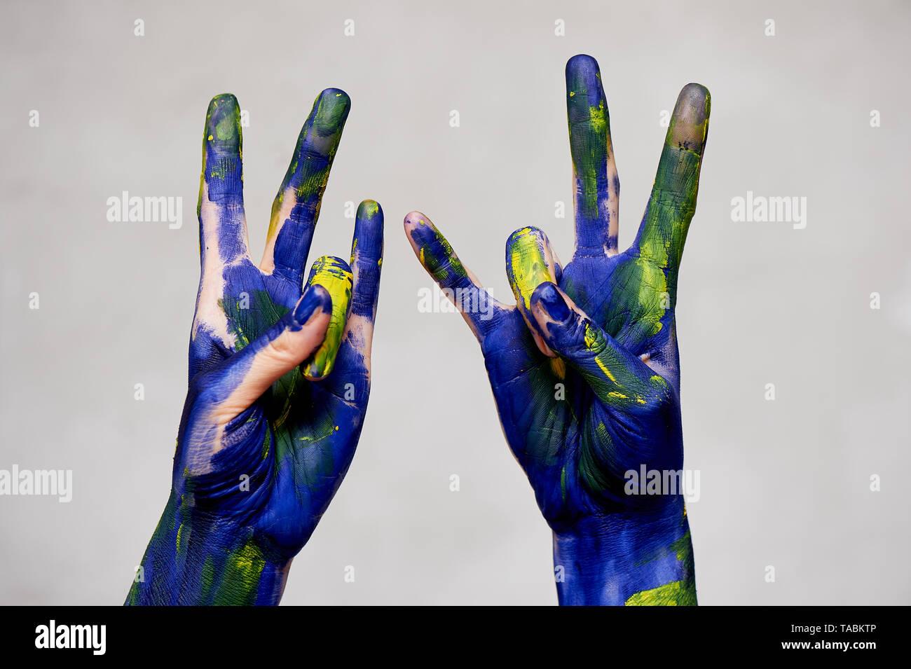 Hände in der blauen Farbe mit gelben Akzenten, Hände an den Künstler und kreative Person. Yoga für die Hände Stockbild