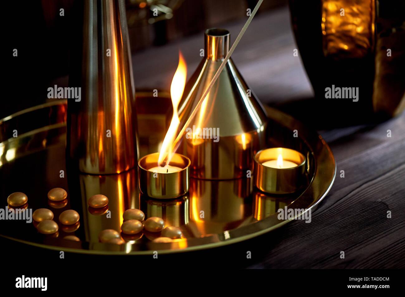 Hand leuchtet eine Kerze mit einer langen Match mit einer hellen Flamme. Die warmen goldenen Gamma. Abend Komfort. Viele Vasen in verschiedenen Formen von gold metall. Stockbild