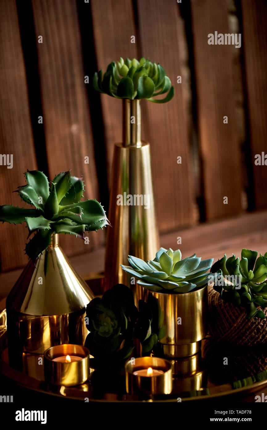 Gemütliche Einrichtung. Gold, brennende Kerzen, goldenen Gefäße, Sukkulenten. Stockbild