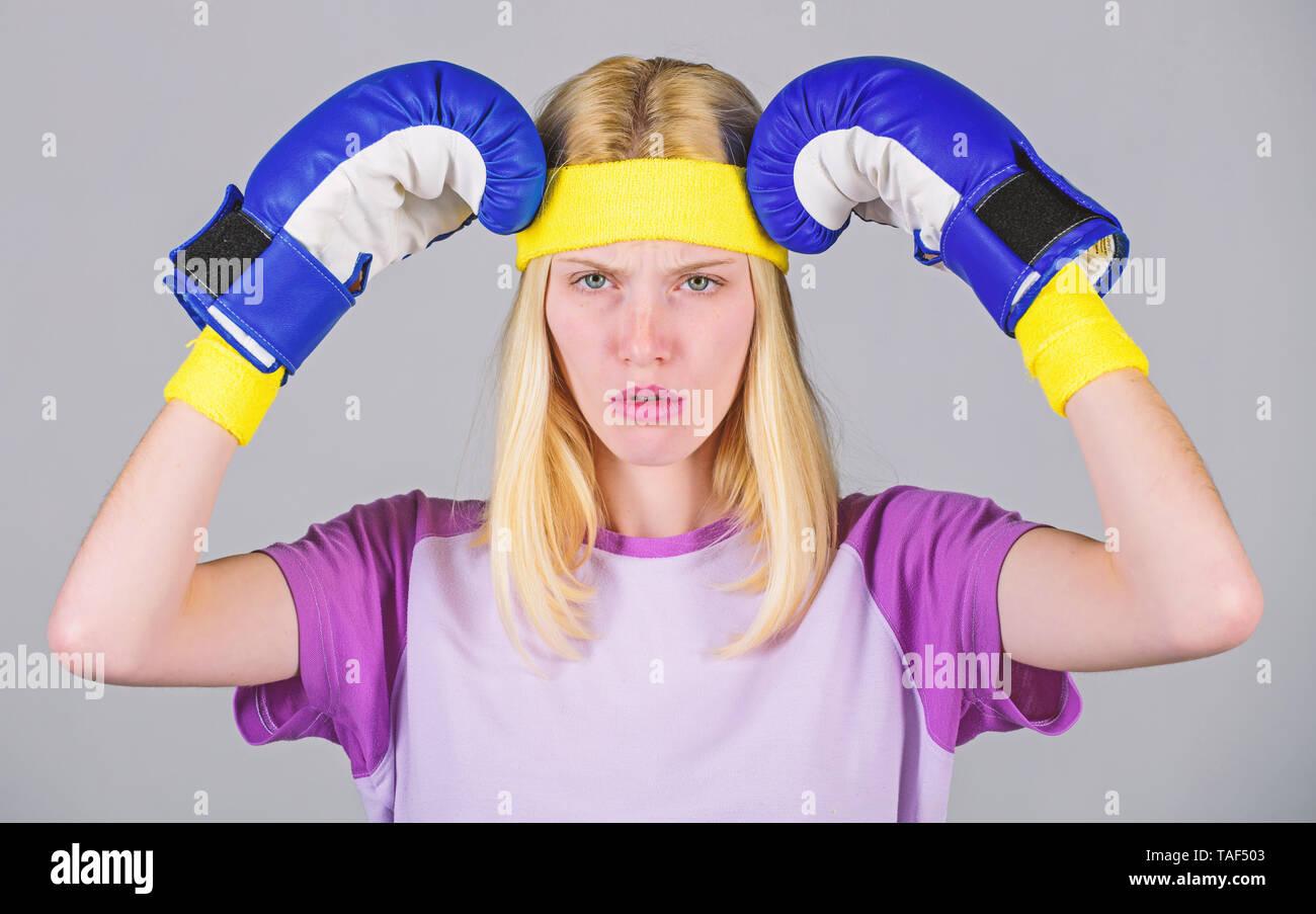 Beat Kopfschmerzen. Mädchen Boxhandschuhe müde zu kämpfen. Starke Frau leiden unter Schmerzen. Mädchen schmerzhafte Gesicht Kopf mit Boxhandschuhen umfassen. Kopfschmerzen Abhilfemaßnahmen. Kopfschmerzen Konzept. Ruhe bewahren und loszuwerden Kopfschmerzen. Stockbild