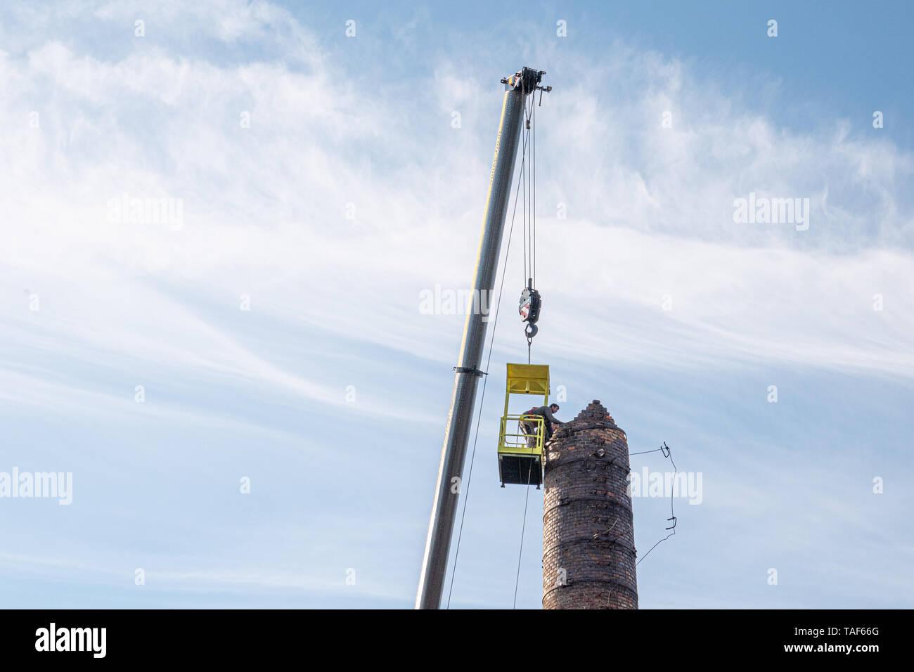 2 Männer in einem Korb hängen von einem riesigen Kran, sorgfältig entfernen einer Fabrik Schornstein Stockfoto