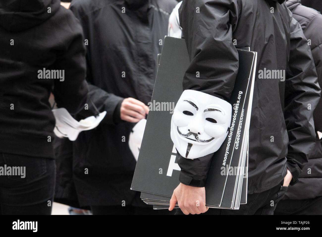 Eine Gruppe junger Leute ganz in Schwarz gekleidet, geht auf die Straße mit anonymen Masken zu demonstrieren. Stockfoto