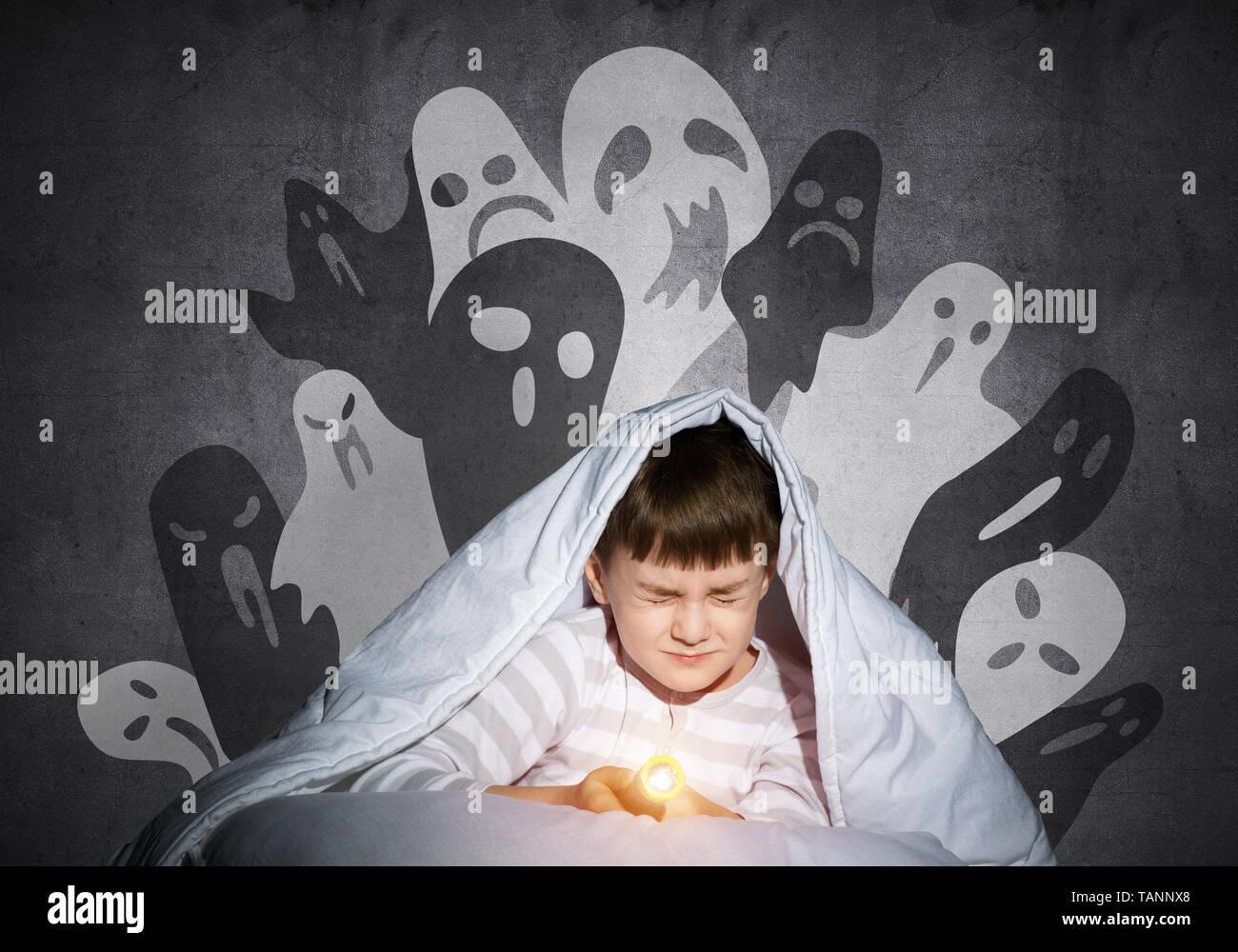Verängstigten Kind mit der Taschenlampe unter der Bettdecke Stockbild