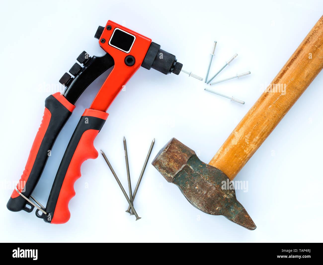 Eine alte Hammer mit einem hölzernen Handgriff und ein paar Nägel gegen neue Niet Pistole und ein paar Nieten Stockbild
