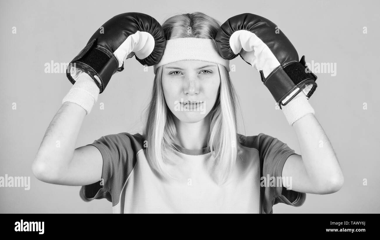 Mädchen schmerzhafte Gesicht Kopf mit Boxhandschuhen umfassen. Kopfschmerzen Konzept. Ruhe bewahren und loszuwerden Kopfschmerzen. Beat Kopfschmerzen. Mädchen Boxhandschuhe müde zu kämpfen. Starke Frau leiden unter Schmerzen. Kopfschmerzen Abhilfemaßnahmen. Stockbild
