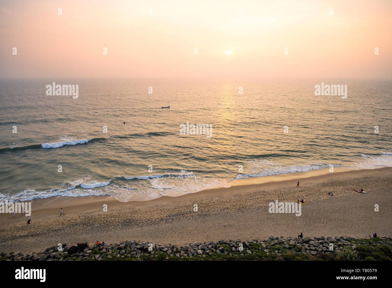 Ansicht von oben, einen atemberaubenden Blick auf einen wunderschönen tropischen Strand mit Menschen Sonnenbaden und genießen einen wunderschönen Sonnenuntergang. Cochin, Kerala, Indien. Stockfoto