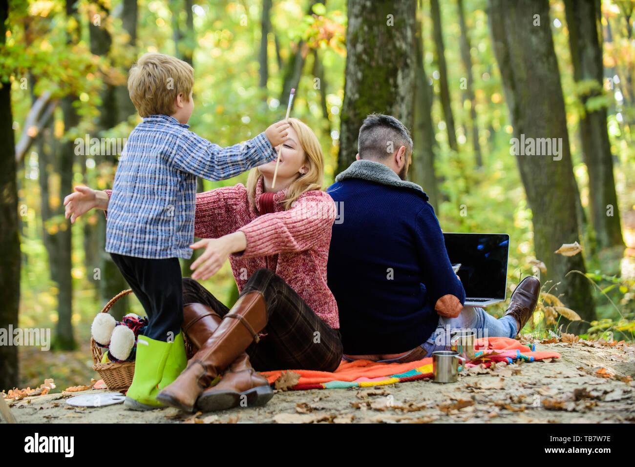 Konflikte, Vati. Familie und Beruf zielen. Vati ist immer besetzt. Tag der Familie Konzept. Familie mit Kind Junge Entspannung in wald. Mutter und wenig spielen zusammen, während der Vater arbeiten mit Laptop. Stockfoto