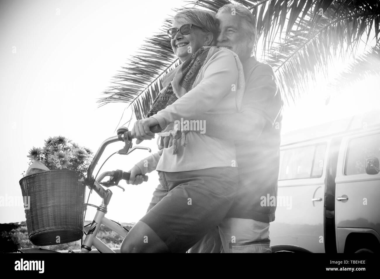 Schönen im Alter von Paar der Älteren in Urlaub gehen beide auf ein altes Fahrrad und genießen Sie den Sommer Sonnenlicht. tropisch und Vintage van im Hintergrund. Schwarz Stockfoto