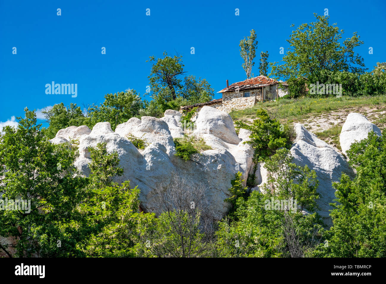 Altes Haus über die Felsen des natürlichen Phänomen Kamenná Svatba oder die Steinerne Hochzeit in der Nähe des Dorfes Zimzelen, Bulgarien Stockbild