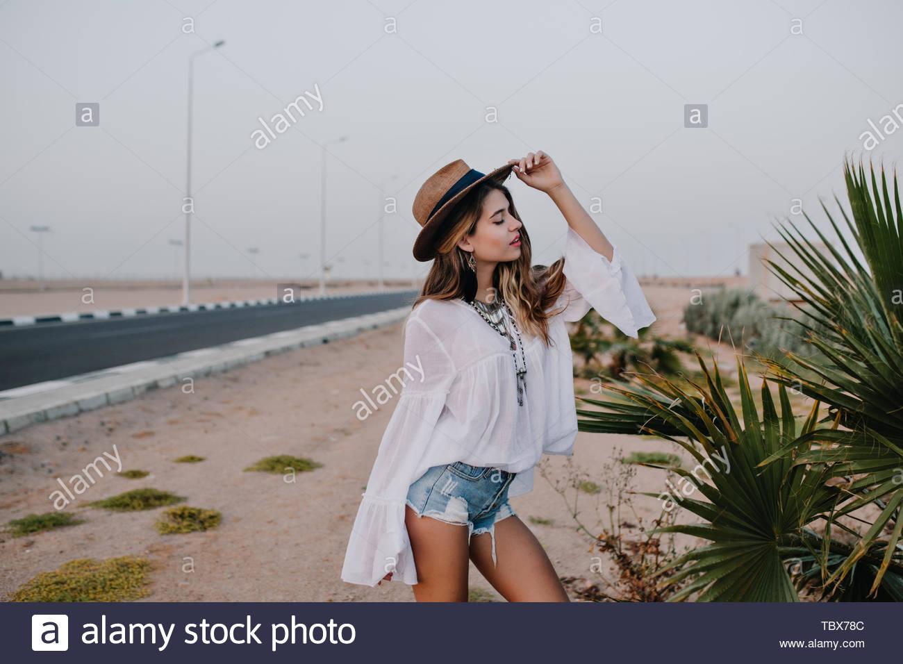 7318280ac31b0c Anmutiges Mädchen tragen weiße Bluse und trendigen Hut posiert mit den  Augen neben exotischen Pflanze vor