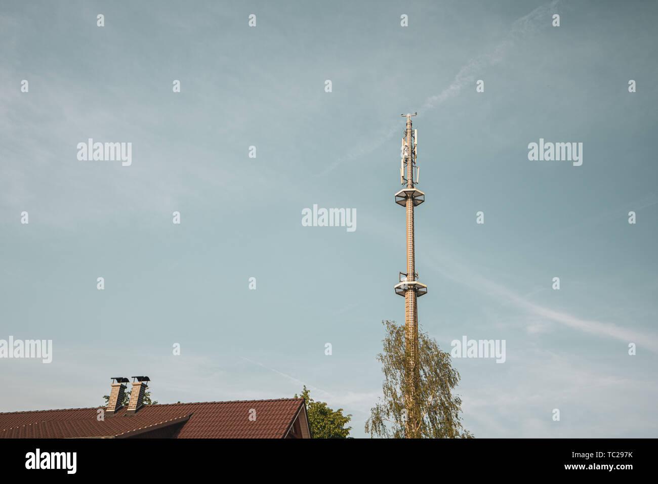 Ein radio Mast für das Mobilfunknetz überragt ein Wohngebäude in den blauen Himmel in einem Wohngebiet. Stockfoto