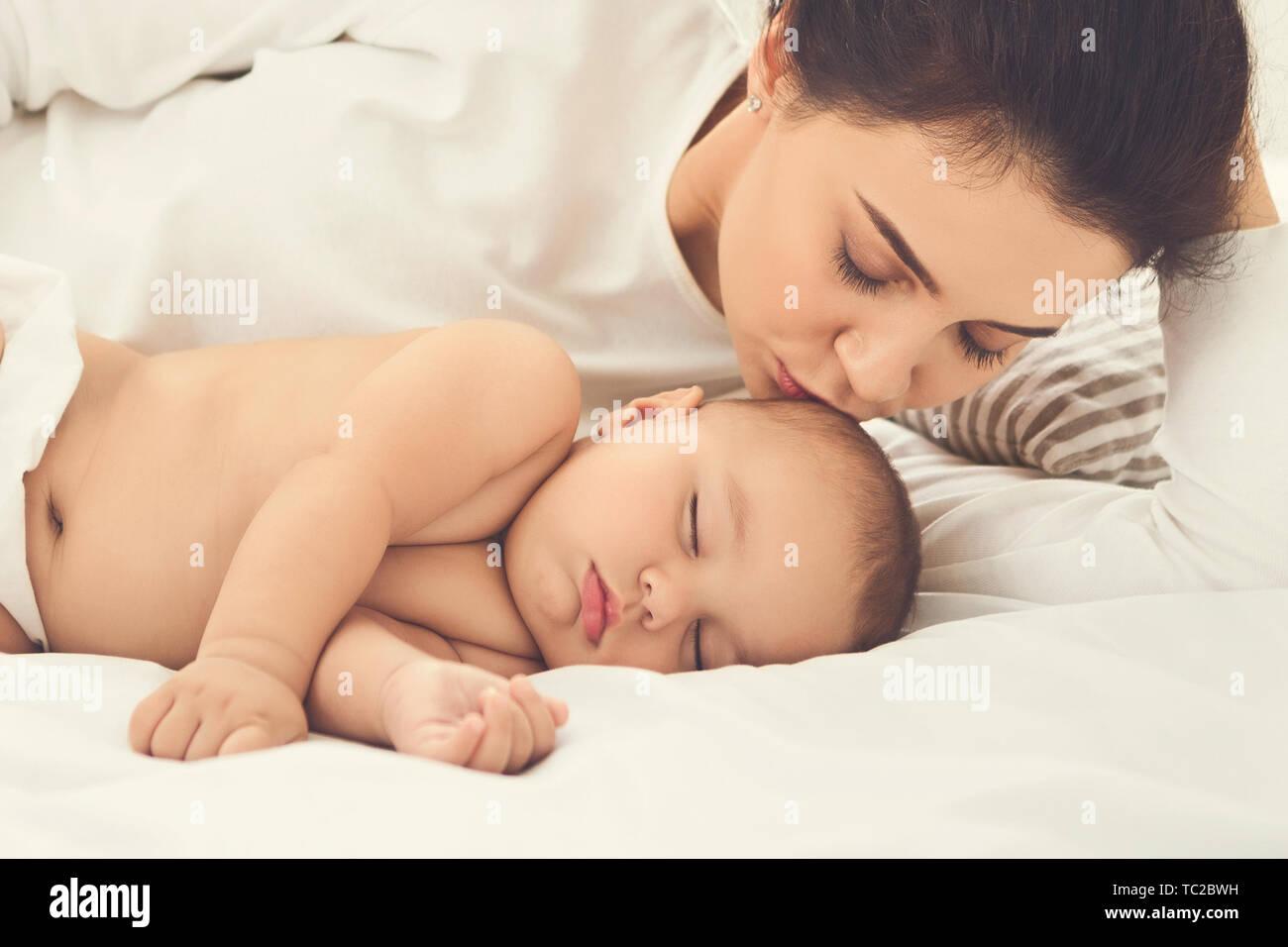 Mutter küssen ihr neugeborenes Baby im Bett schlafen Stockfoto
