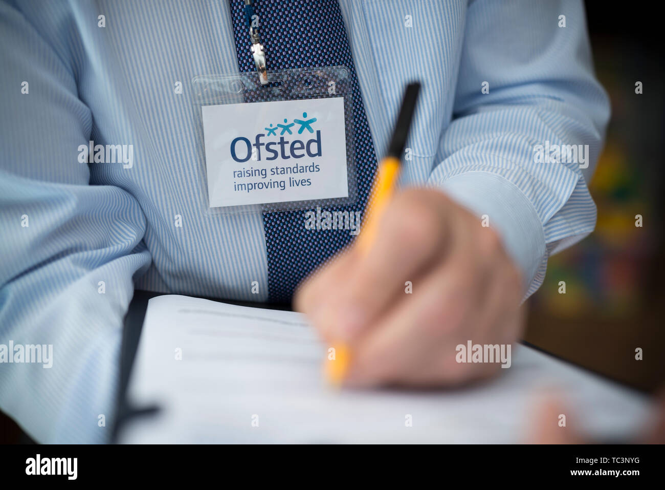 Ein Mann in einem Hemd und Krawatte mit einem ofsted Lanyard gekleidet zu sein scheint, die Erstellung eines Berichts mit einem Stift und Zwischenablage. (Nur redaktionelle Nutzung) Stockbild