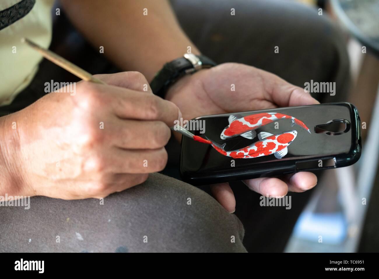 Thailand, Chiang Mai Provinz, Bor Sang. Regenschirm factory. Ein Arbeitnehmer, der malt Eine handphone Gehäuse. Stockbild