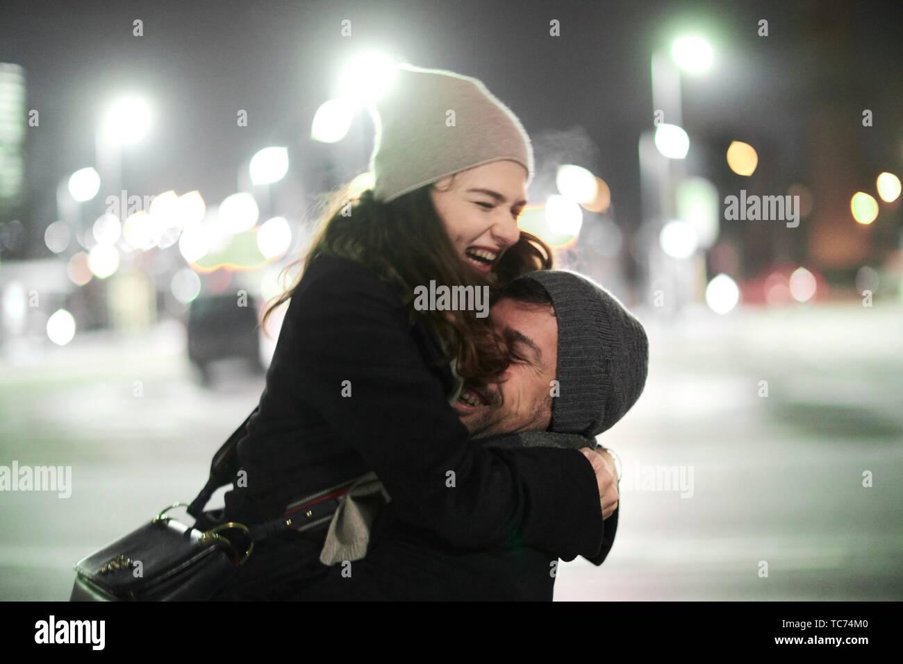 Paar in die Arme fallen, umarmen, lachen Liebhaber draußen in der Stadt in der Nacht, Glück, in München, Deutschland. Stockfoto