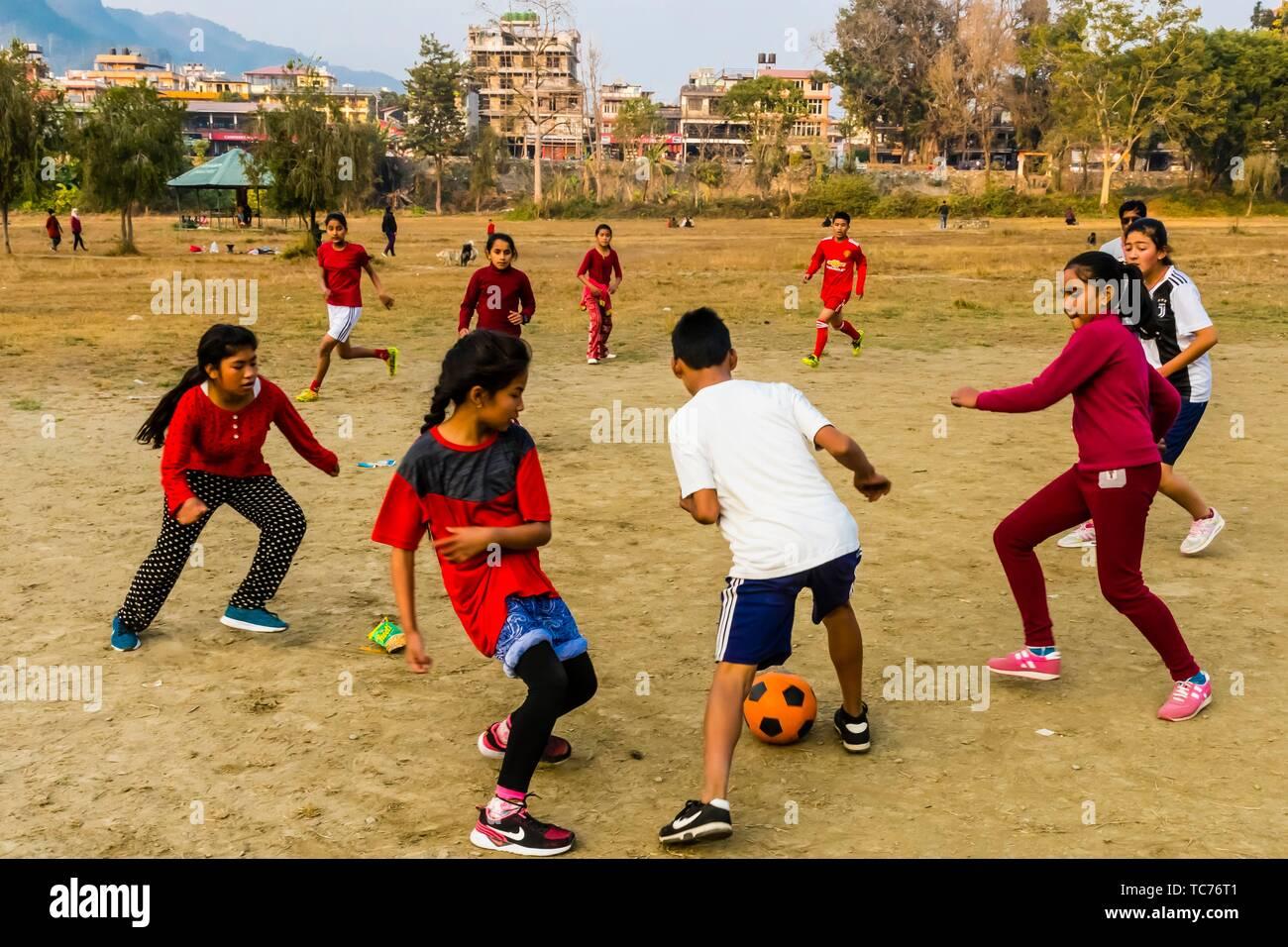 Mädchen und Jungen Fußball spielen, Lakeside, Pokhara, Nepal. Stockbild