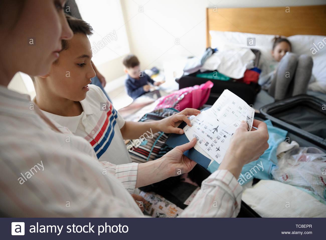 Familie mit Flugtickets packen Koffer für den Urlaub auf dem Bett Stockbild