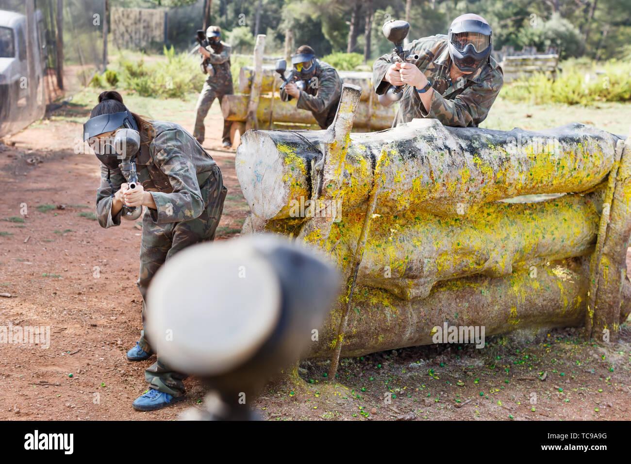 Paintball Spieler zielen und schießen mit dem Marker Gewehren an einem gegnerischen Team im Freien Stockfoto