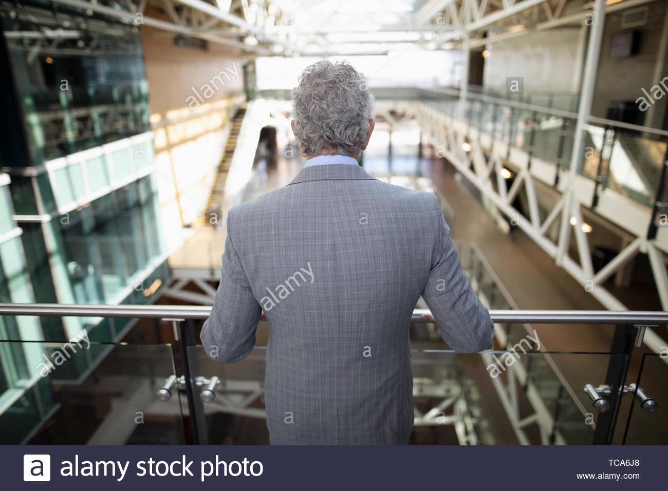 Senior Geschäftsmann an Büro atrium Balkon Stockbild