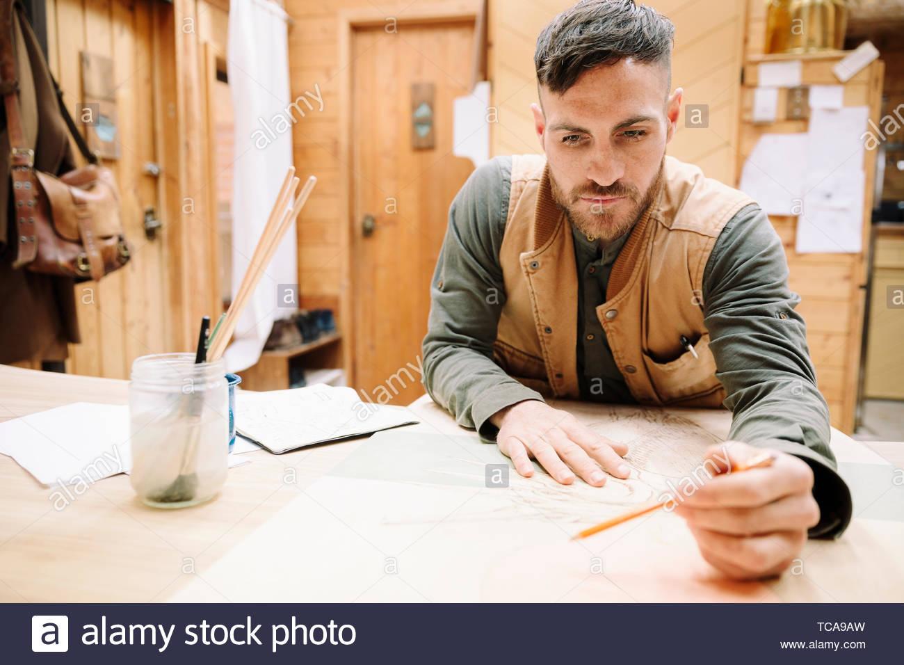 Fokussierte männliche Künstler Zeichnung am Tisch Stockbild