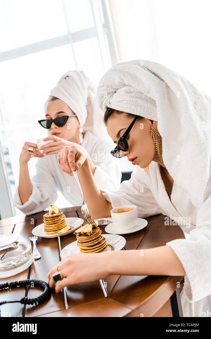 Stilvolle Frauen in Bademänteln, Sonnenbrillen und Schmuck mit Handtüchern auf Staats- und Pfannkuchen essen für Frühstück Stockfoto