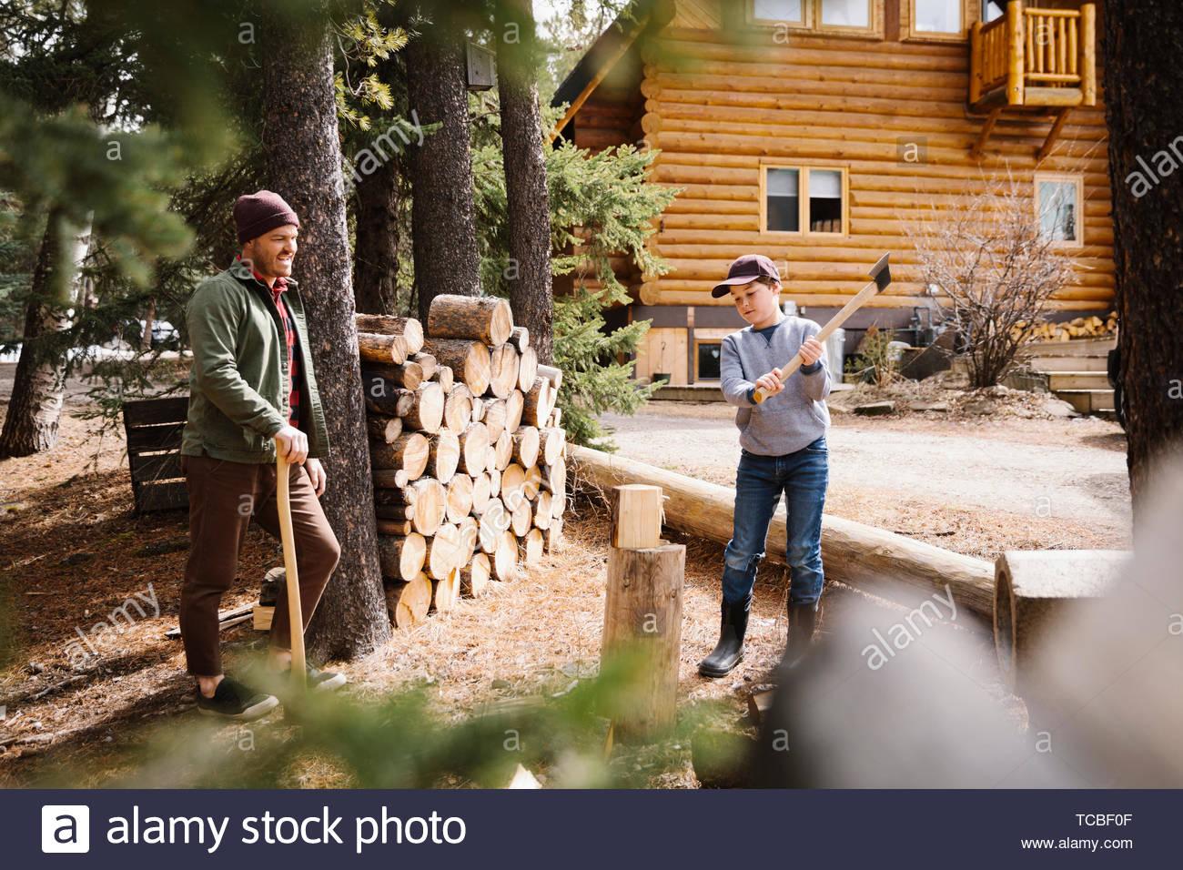 Vater lehre Sohn wie Brennholz aussen Kabine zu schneiden Stockbild