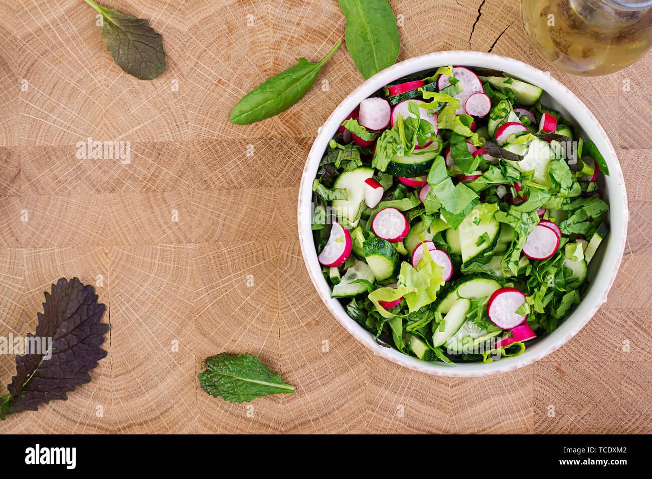 Frischer Salat aus Gurken, Radieschen und Kräutern. Flach. Ansicht von oben Stockfoto