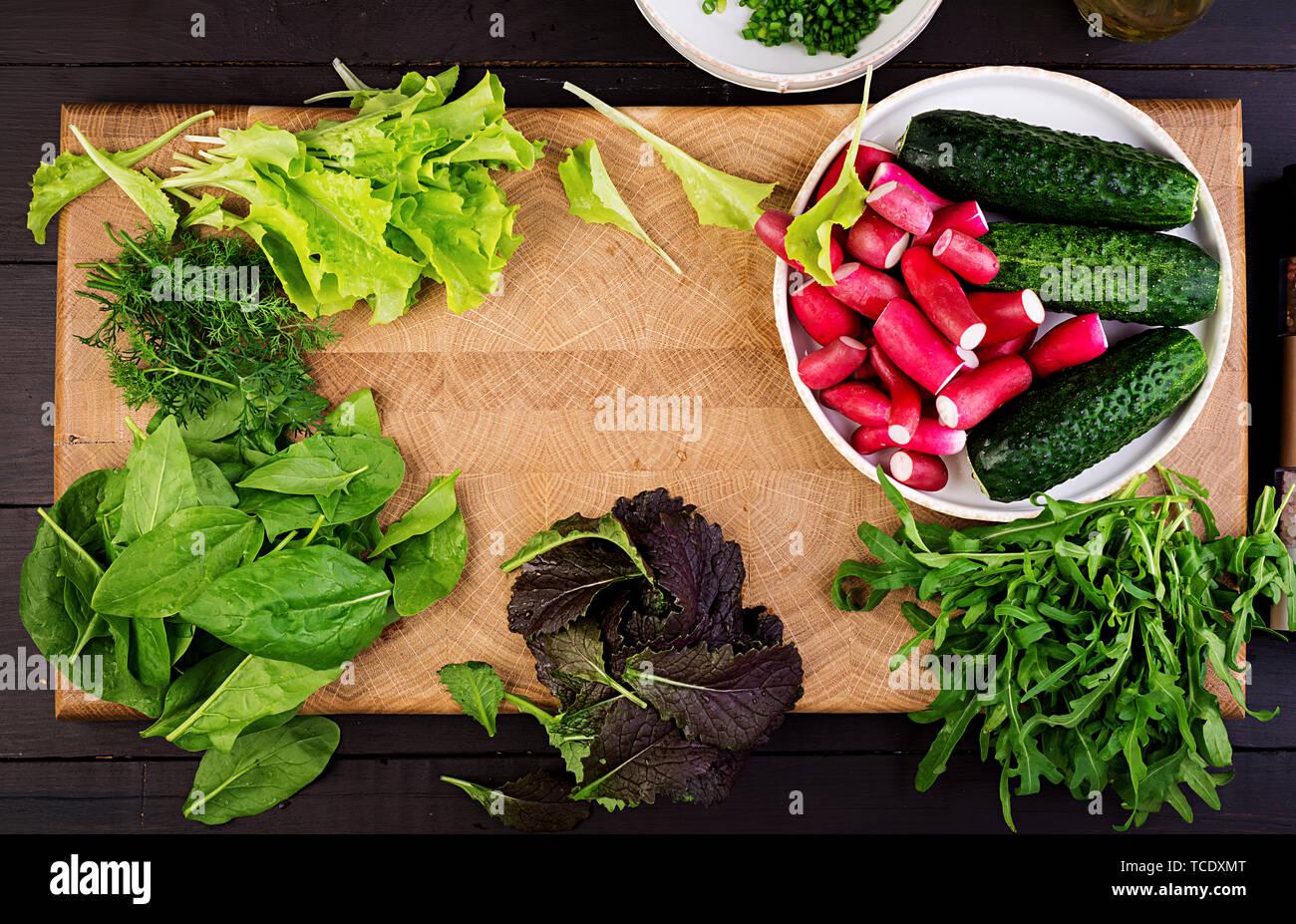 Zutaten für frischen Salat aus Gurken, Radieschen und Kräutern. Flach. Ansicht von oben Stockfoto