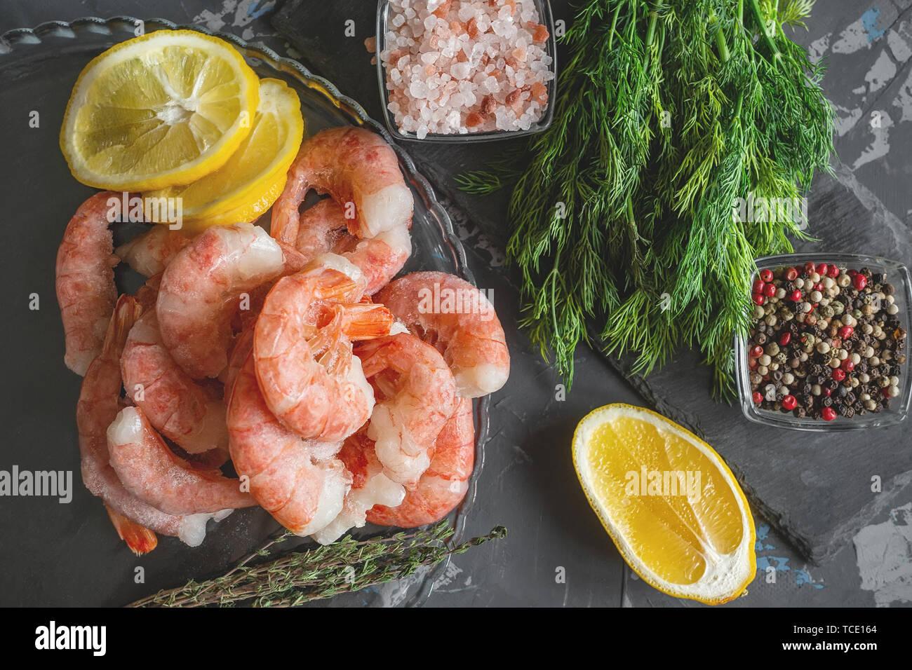 Gefrorene Garnelen werden zum Kochen bereit. Garnelen mit Zitrone farbige Gewürze bohnenkraut Pfeffer Dill und Meersalz. Zubereitung Stockbild