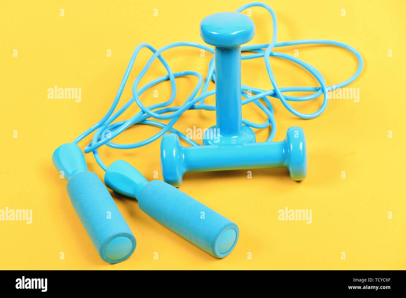 Hanteln und Seil springen in Cyan blaue Farbe auf gelbem Hintergrund. Gestaltung und Fitnessgeräte. Hanteln und Springseil in der Nähe von einander gesetzt. Sport und gesunde Lebensweise Konzept Stockbild