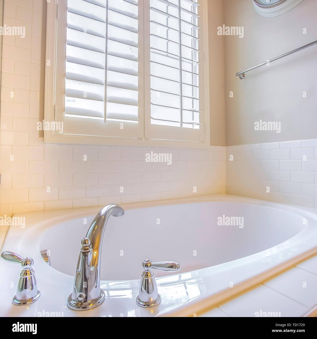 Platz in Badewanne und Fenster mit Jalousien im Badezimmer ...