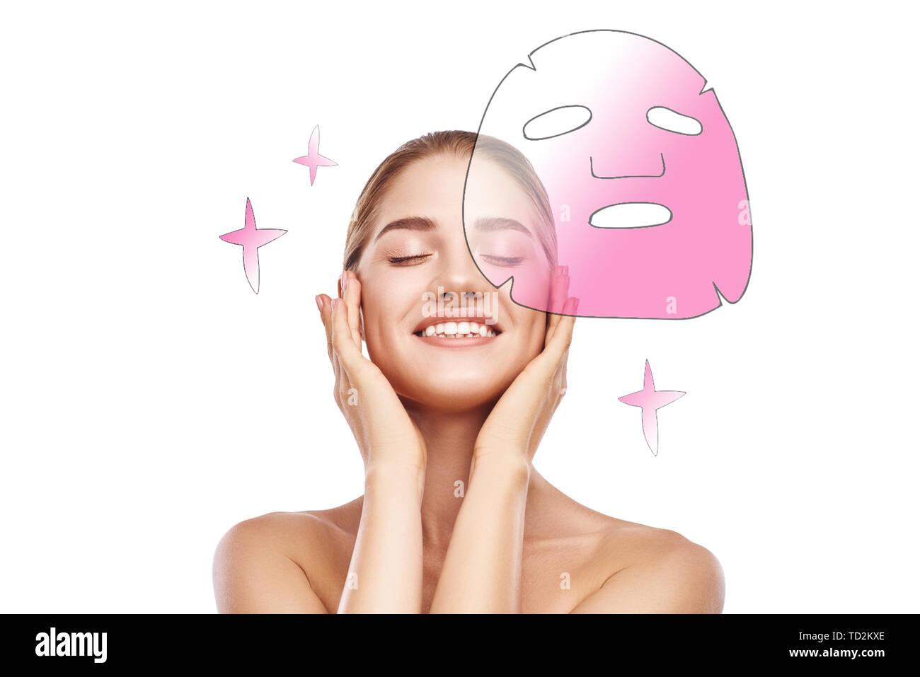 Lassen Sie sich verwöhnen! Portrait von lächelnden jungen Frau mit geschlossenen Augen berühren ihre perfekte Haut und Kosmetik Maske im Gesicht anwenden im Stehen Stockbild