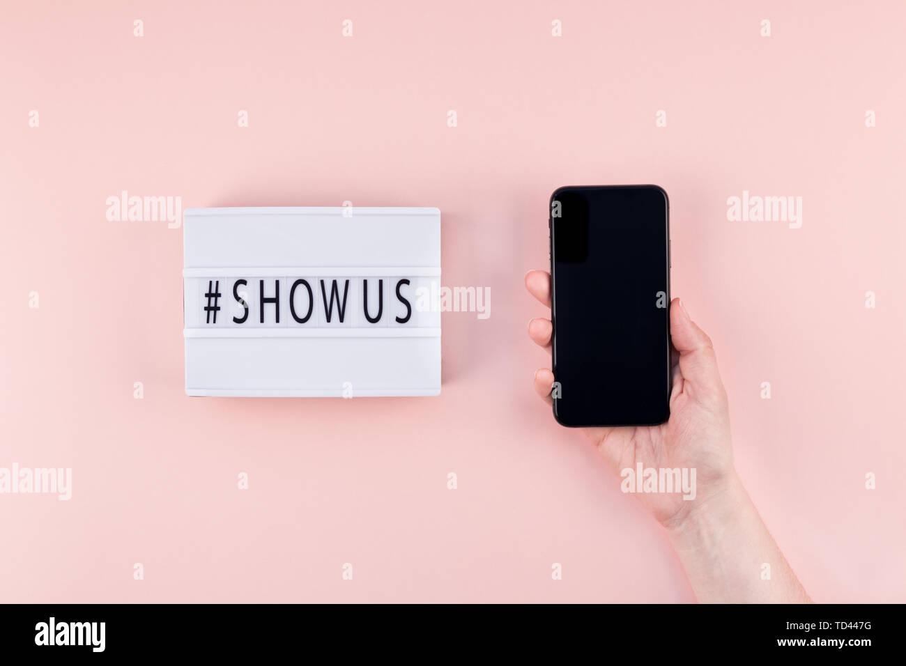 Kreative, oben flach der Lightbox mit hashtag zeigen uns Nachricht und Handy in der Hand mockup rosa Hintergrund minimal Style. Konzept Projekt wor Stockbild