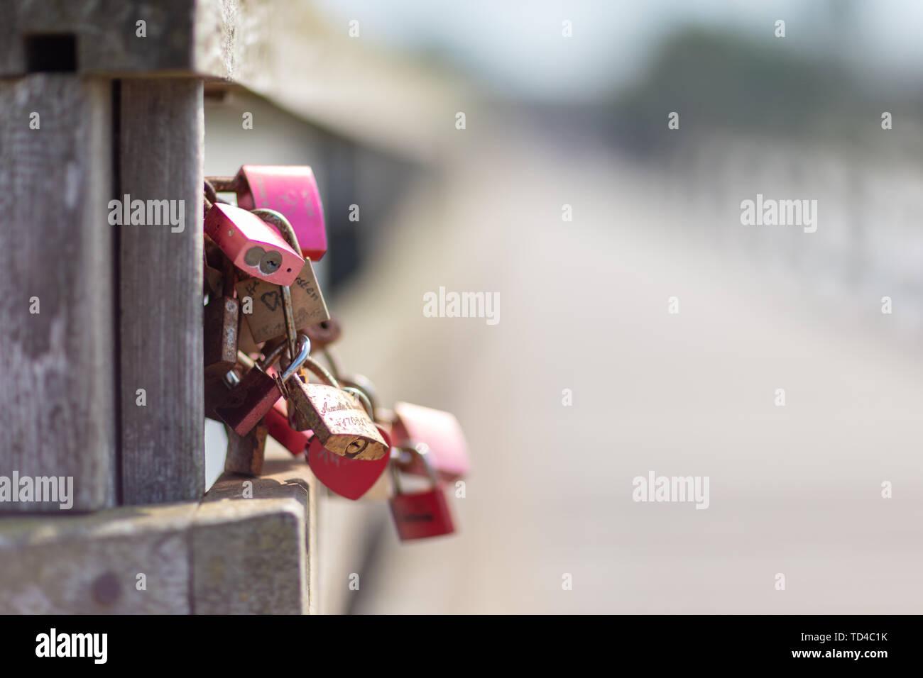 Graviert Vorhängeschlösser hängen auf einer Brücke als Symbol für Liebhaber Stockfoto