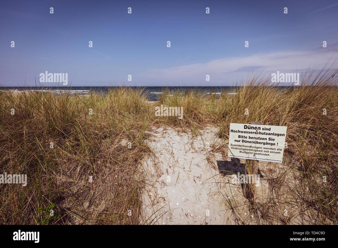 Ein Schild mit einem Warnschild steht an der Düne von der Ostsee Se Stockfoto