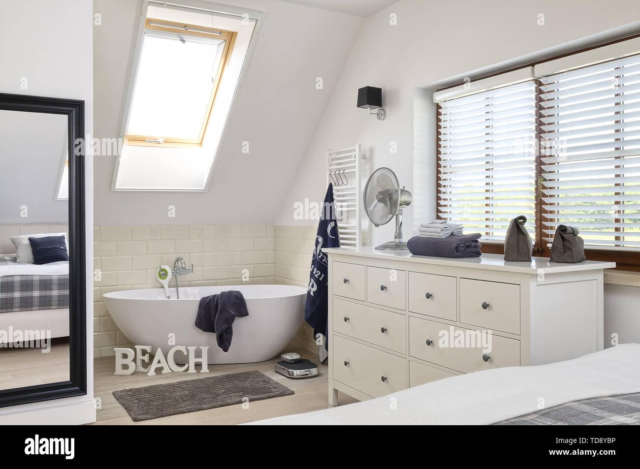 Freistehende Badewanne und Kommode in offenen Schlafzimmer ...