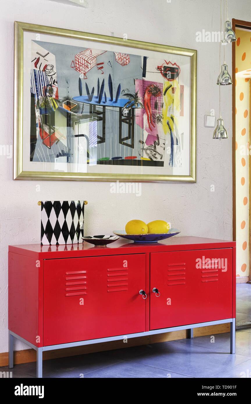Gerahmte moderne Malerei über den red Metallschrank neben ...