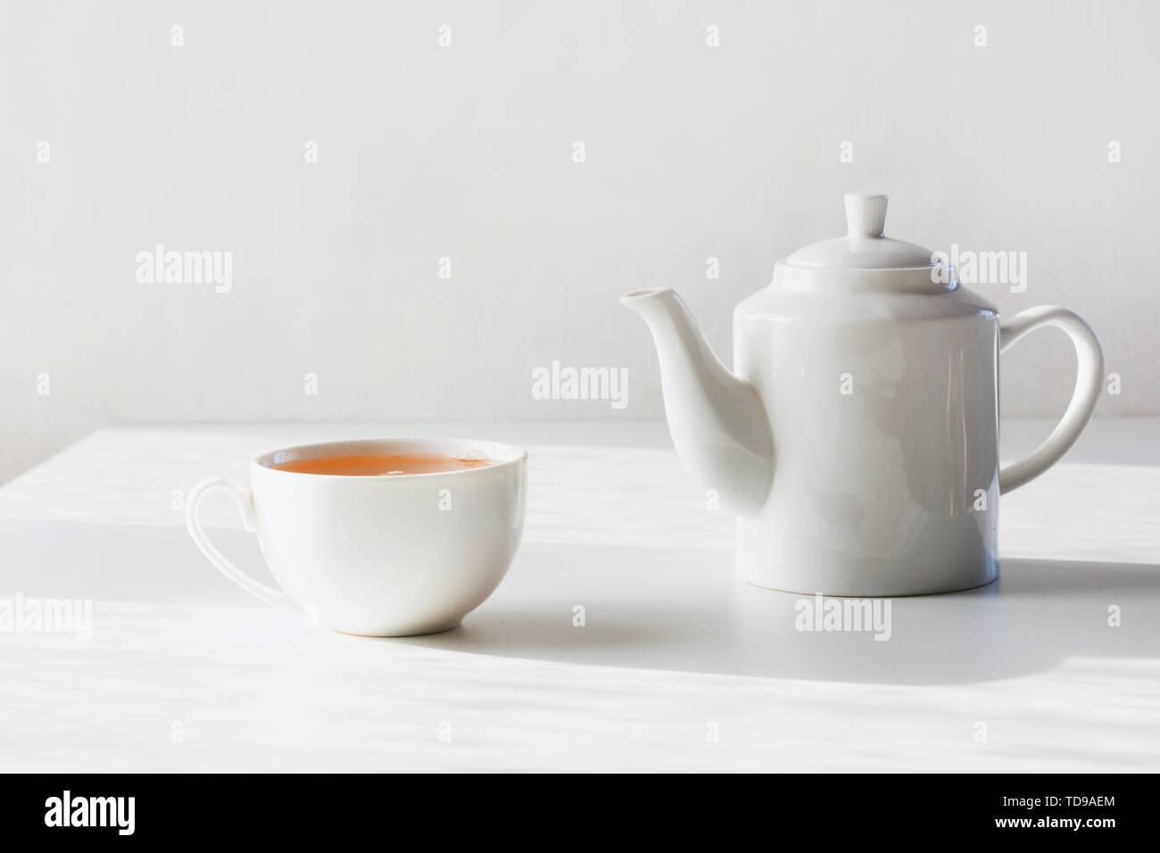 Zeit für Tee. Satz von Schale und Teekanne auf Weiß. Minimale Zusammensetzung. Close Up. Stockbild