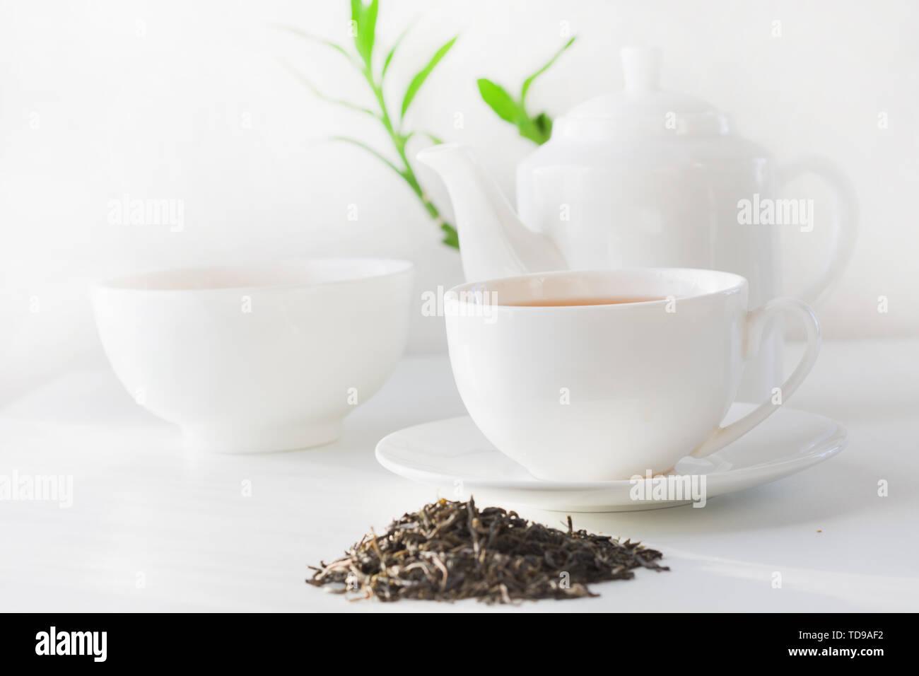 Noch immer leben Tasse grünen Tee, Teekanne mit grüner Tee trockene Blätter auf Weiß. Teatime. Stockbild