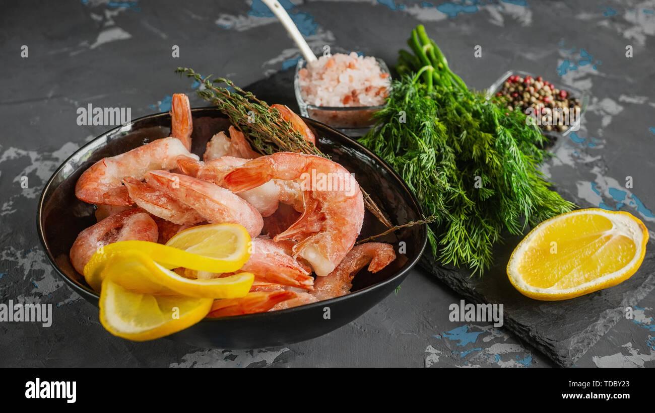 Gefrorene Garnelen werden zum Kochen bereit. Garnelen mit Zitrone farbige Gewürze bohnenkraut Pfeffer Dill und Meersalz. Zubereitung von Speisen. Stockbild