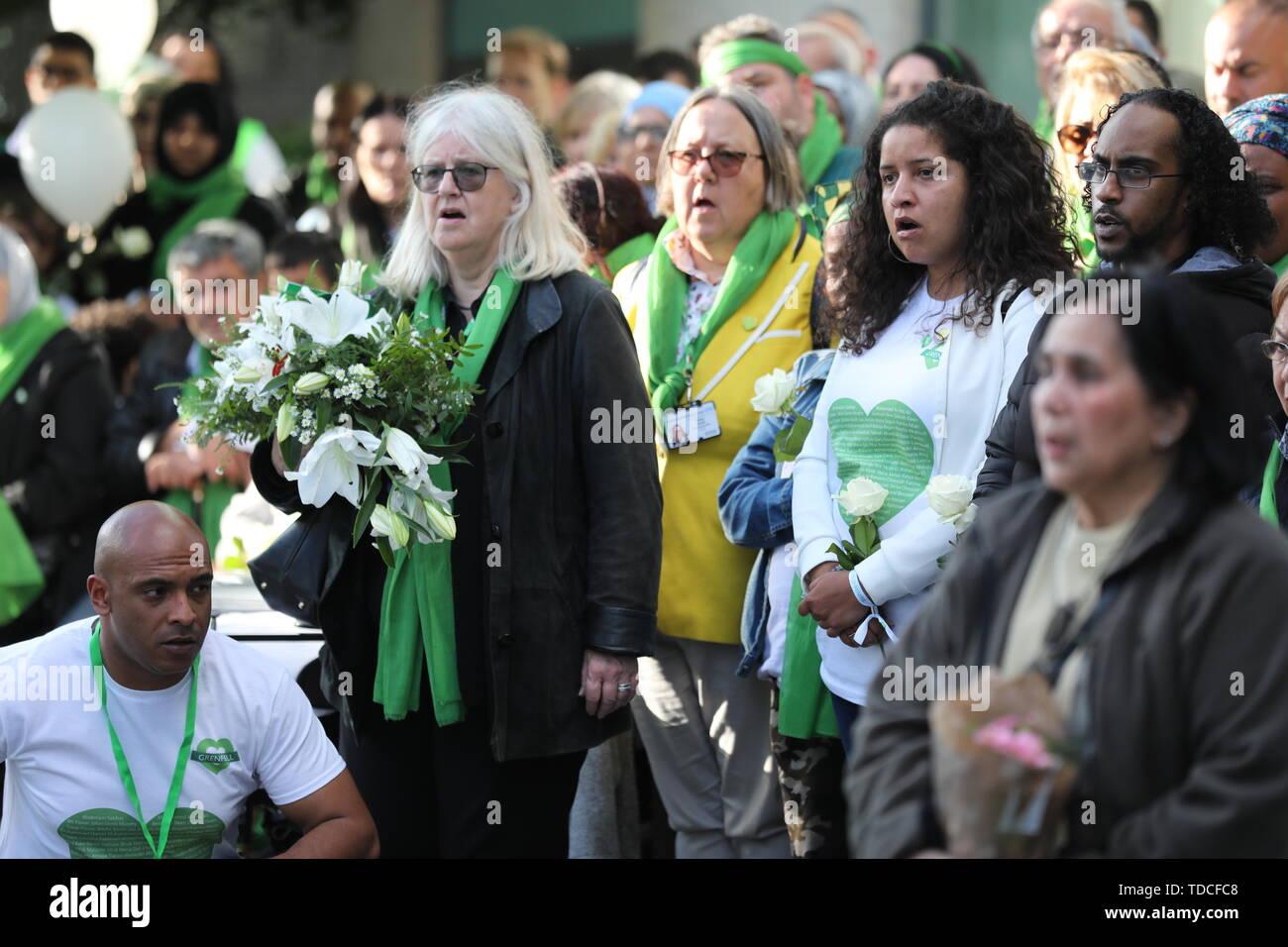 Familie und Freunde der 72 Menschen, die ihr Leben in der Grenfell Hochhaus verloren zu einem Chor Begleitung vor einer Kranzniederlegung Zeremonie ausserhalb Grenfell Tower, London, anlässlich des 2-jährigen Jubiläum singen. Stockbild