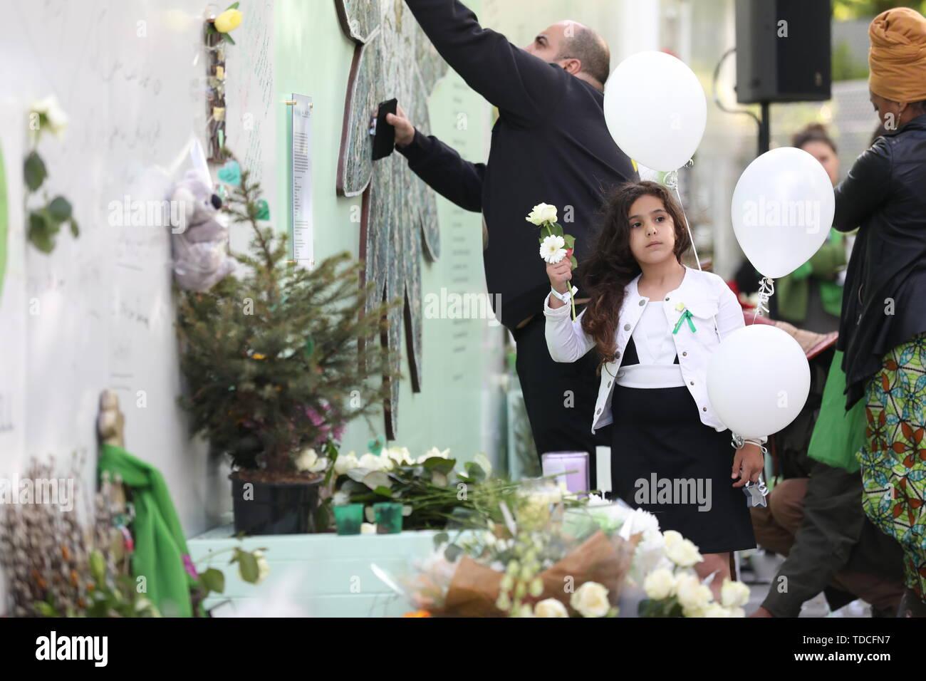 Familie und Freunde der 72 Menschen, die ihr Leben in der Grenfell Hochhaus verloren legen Blumen und Nachrichten, die während einer Kranzniederlegung Zeremonie ausserhalb Grenfell Tower, London, anlässlich des 2-jährigen Jubiläum schreiben. Stockbild