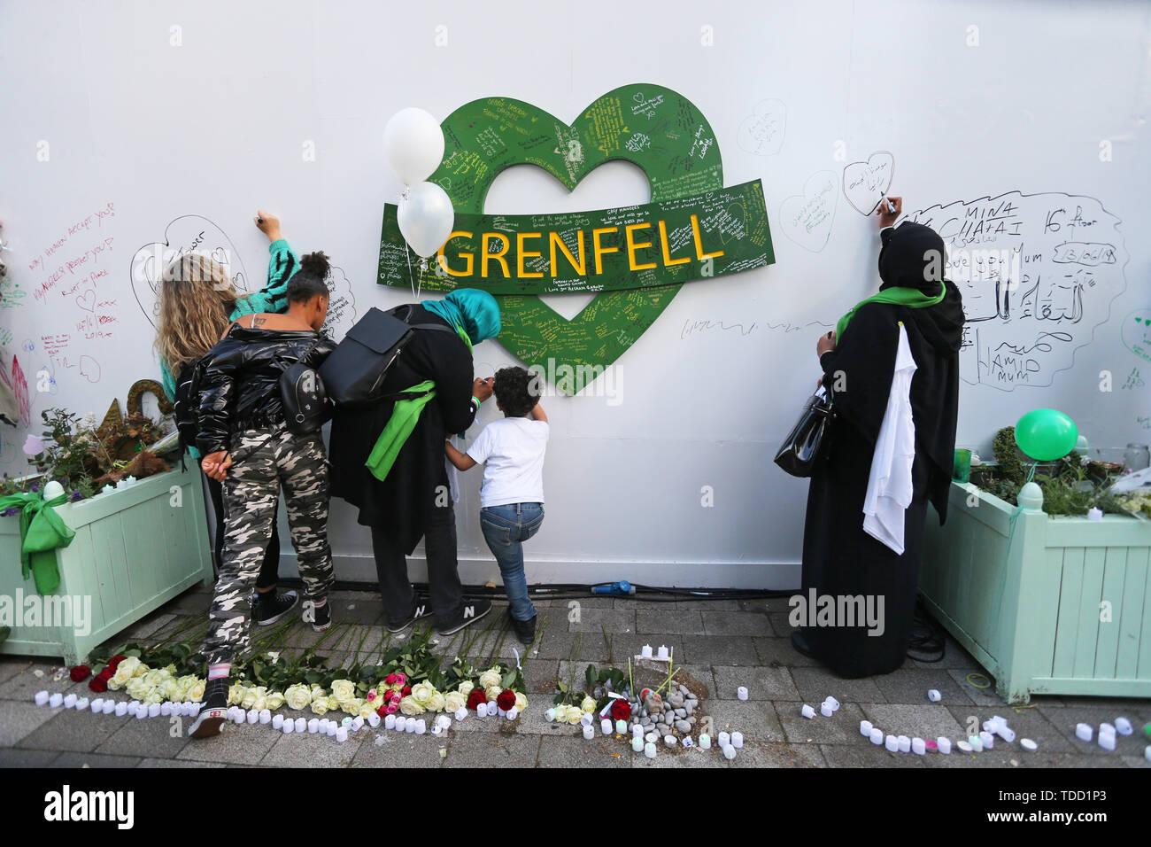 Familie und Freunde der 72 Menschen, die ihr Leben in der Grenfell Hochhaus verloren Nachrichten, die während einer Kranzniederlegung Zeremonie ausserhalb Grenfell Tower, London, anlässlich des 2-jährigen Jubiläum schreiben. Stockbild