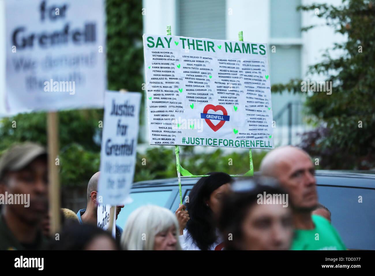 Eine Liste mit den Namen der 72 Menschen, die ihr Leben in der Grenfell Hochhaus Feuer auf ein Zeichen verloren, außerhalb Grenfell Tower, London, während ein stiller Spaziergang zum zweijährigen Jubiläum. Stockbild